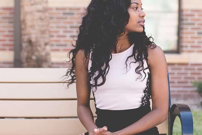 dicas para fazer o cabelo crescer - moça negra sentada em uma cadeira olhando para o lado
