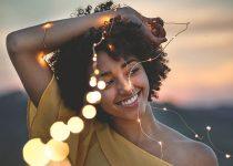 mulher com cabelo crespo sorrindo e olhando para o lado