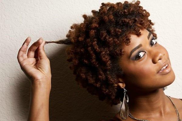mulher de cabelo afro e curto pós transição capilar