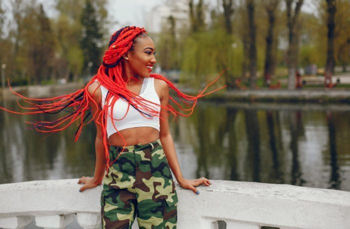 box braids a young and stylish dark skinned girl with red dreads walking in the summer park near river 1157 14226 700x458 8155124 1218421