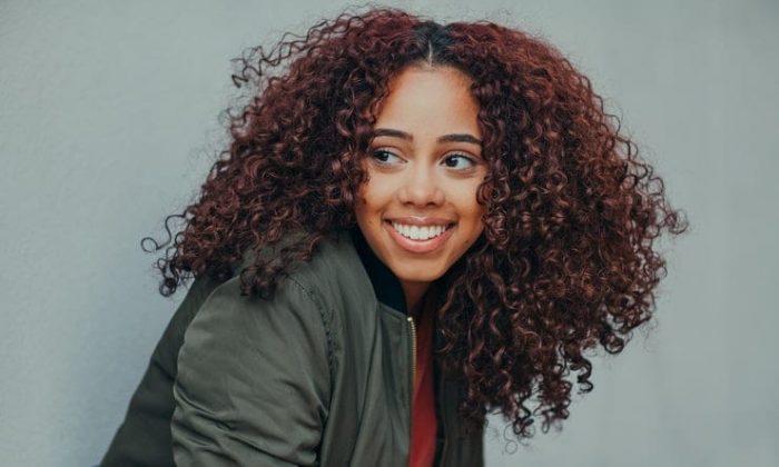 moça sorrindo com cabelos crespos tingidos de vermelho