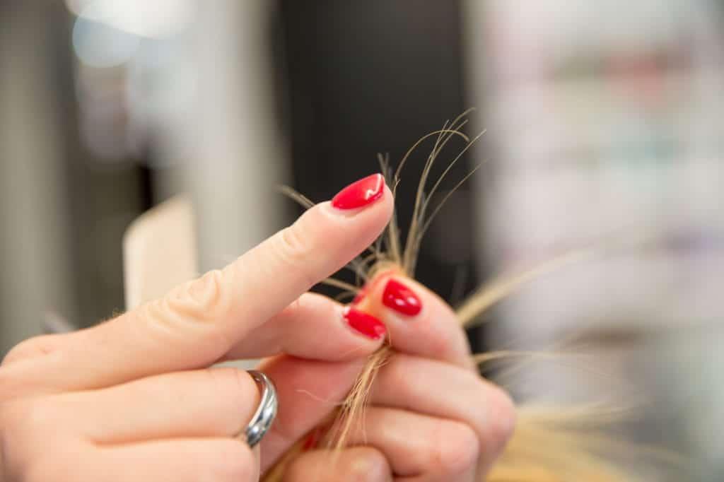 mãos segurando as pontas dos cabelos e verificando pontas duplas