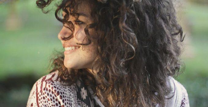 moça com o cabelo cacheado olhando para o lado
