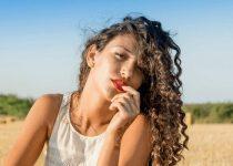 moça com cabelo crespo sentada em um campo ao sol