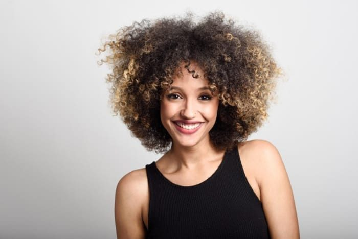 Cabelos curtos Cortes femininos woman smiling face with curly hair 1139 582 700x468 9230943 6924276