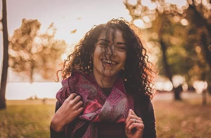 mulher com cabelo cacheado sorrindo