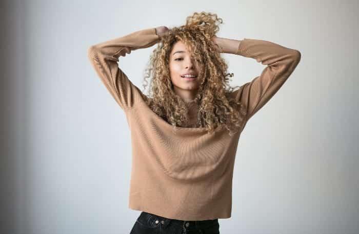 mulher negra loira colocando as mãos em seus cabelos cacheados