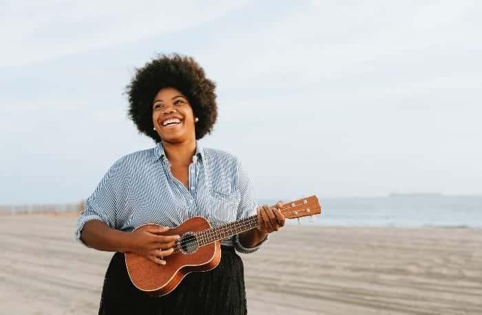 Moça com cabelo afro 4c segurando um violão e sorrindo