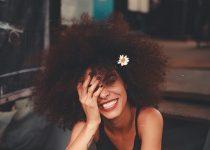 mulher cacheada com flor no cabelo